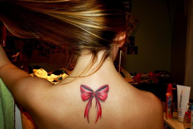 Grey Ink Ribbon Bow Tattoo On Back Neck photo - 1