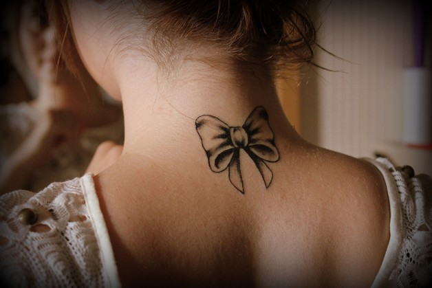 Lovely Pink Cancer Ribbon Tattoo On Back Neck photo - 1