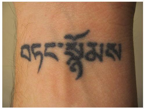 black ink buddhist tattoo on wrist photo - 2