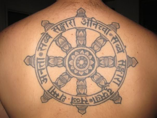 grey ink buddhist wheel tattoo on upper back photo - 1