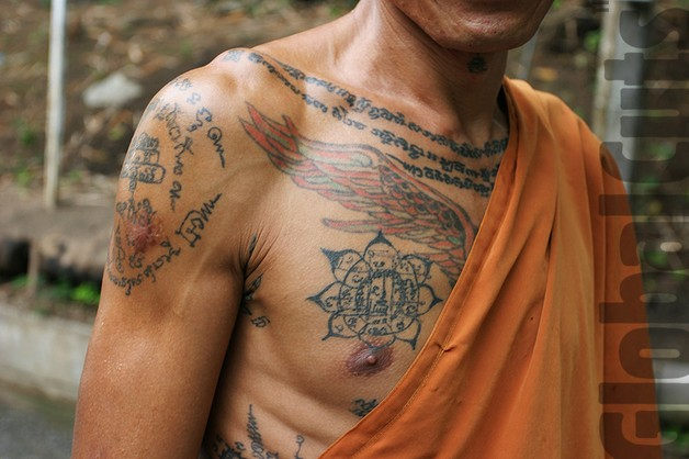 red ink buddhist tattoo on shoulder photo - 1