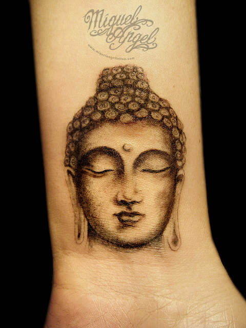 shining buddhist tattoo on wrist photo - 1